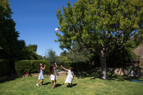 Female friends playing with balloon at yard - CAVF41832