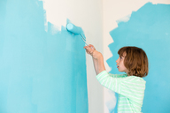 Side view of girl painting wall at home - CAVF41844