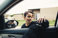 Boy petting dog sitting in car - CAVF41853