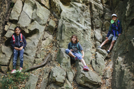 Low angle portrait of happy siblings climbing on rocks - CAVF41856