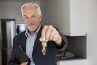 Portrait of confident real estate agent holding new house keys - MASF04817