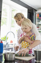 Mother teaching daughter to cut vegetables in kitchen - MASF04823