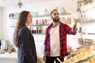 Owner showing products to customer in candy store - MASF04835