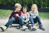 Playful friends sitting on skateboard at yard - MASF04847