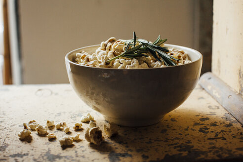 Bowl of popcorn with rosemary on table - CAVF41927