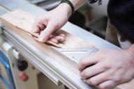Cropped hands of carpenter measuring wooden planks at workshop - CAVF41933