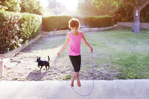 Girl jumping with rope on field - CAVF41999