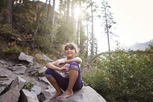 Happy girl sitting on rock against trees in forest - CAVF42029