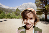 Portrait of smiling girl on field against mountains - CAVF42035