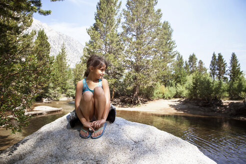 Girl sitting on rock by river against trees - CAVF42038