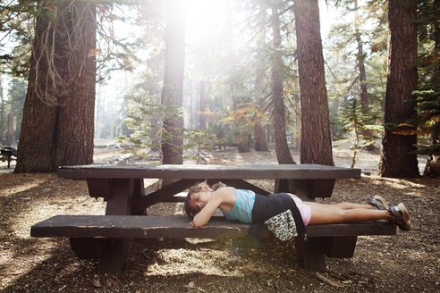 Side view of girl lying on bench amidst trees in forest - CAVF42041