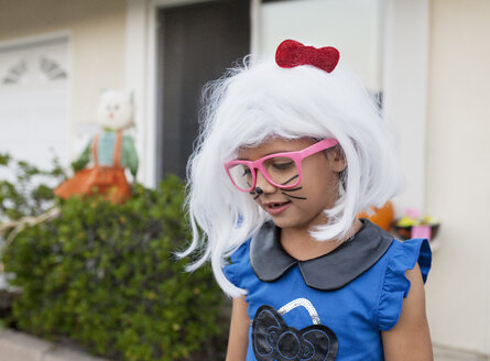 Cute girl with whiskers painted on face wearing white wig outside house - CAVF42113
