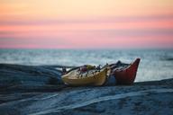 Kayaks on rock at sea during sunset - MASF04868
