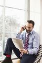 Mid adult businessman reading document while on call by office window - MASF04889