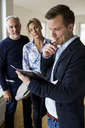 Male real estate agent reading agreement with couple standing in background at home - MASF04892