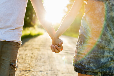 Midsection of couple holding hands on dirt road against bright sun - MASF04904