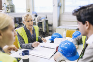 Mature female worker having discussion with colleagues at table in factory - MASF04913