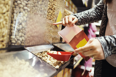 Midsection of woman filling pistachio nuts in paperbag at supermarket - MASF04916