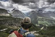Rear view of hiker standing against mountain range - CAVF42124