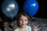 Portrait of girl holding balloons while standing at home - CAVF42343