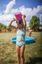 Girl pouring water on head while standing on grassy field at backyard - CAVF42370