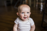 Portrait of happy baby girl sitting at home - CAVF42382