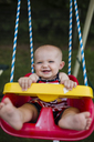 Portrait of baby girl swinging at playground - CAVF42394