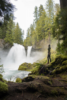 Side view of female hiker looking at waterfall while standing on mossy rock - CAVF42502