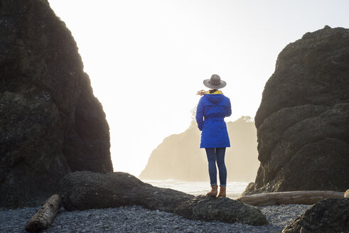 Rear view of female hiker standing at Ruby Beach against clear sky - CAVF42511
