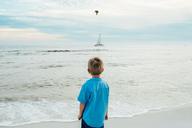 Rear view of boy standing at Panama City Beach - CAVF42541