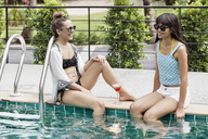 Happy female friends relaxing at poolside - CAVF42694