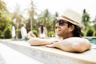 Thoughtful man relaxing in swimming pool at tourist resort - CAVF42715