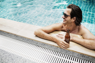 High angle view of man holding beer bottle in swimming pool - CAVF42718