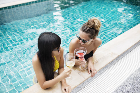 High angle view of women toasting drinks in swimming pool - CAVF42724