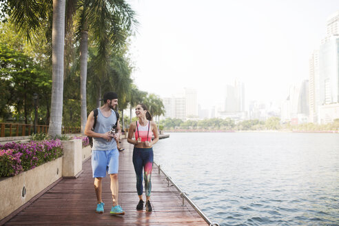Couple smiling and walking on wooden walkway at riverbank - CAVF42751