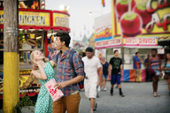 Happy couple playing while having popcorn at amusement park - CAVF42808