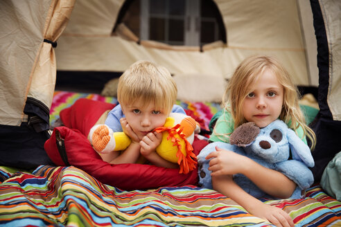 Portrait of siblings with stuffed toys lying in tent - CAVF42820