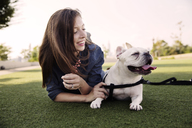 Happy woman lying with dog on grassy field at park - CAVF42859