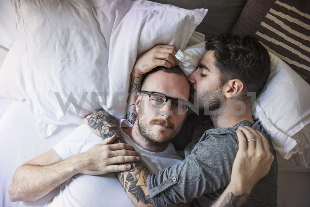 Man kissing boyfriend while lying on bed at home - CAVF43009