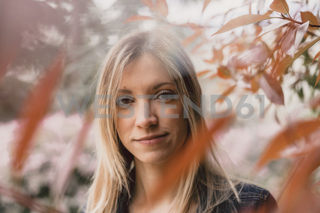 Portrait of smiling young woman in nature - AFVF00437