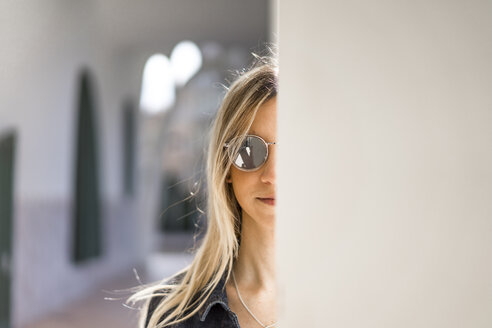 Portrait of young woman wearing mirrored sunglasses hiding behind column - AFVF00440