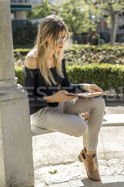 Young woman with notebook sitting on bench - AFVF00446