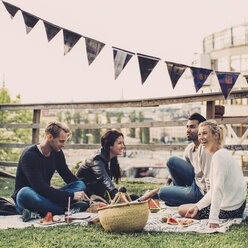 Happy friends enjoying picnic on roof garden - MASF04935