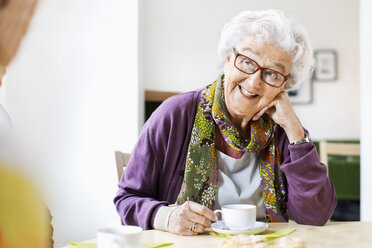 Happy senior woman looking at friend while having coffee at breakfast table in nursing home - MASF04944