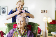 Happy female caretaker putting curlers to senior woman's hair at nursing home - MASF04947