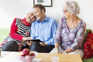 Happy senior couple using digital tablet by female friend in nursing home - MASF04950