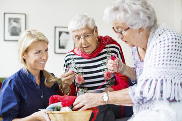 Happy female caretaker looking at senior women choosing wool for knitting at nursing home - MASF04953