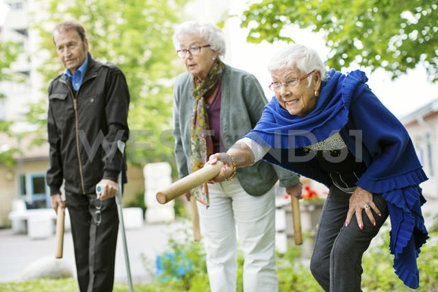Happy senior people playing kubb game at park - MASF04956