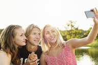 Happy friends taking selfie while having breakfast by lake against clear sky - MASF04989