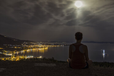 Greece, Pagasetic Gulf, Woman enjoying view to Volos at night, full moon - MAMF00060